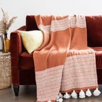 VAGLIA - Baumwolldecke, terrakottafarben mit weißen Grafikmustern und Quasten 160x120